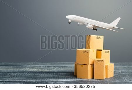 Cardboard Boxes And Freight Airplane. International Delivery Distribution Of Goods And Products. Log