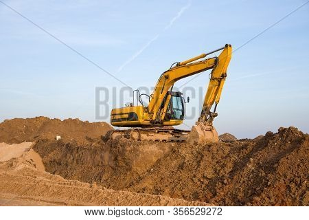 Excavator Working At Construction Site. Backhoe Digs Ground For The Foundation And For Paving Out Se