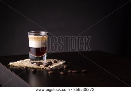 B-52 Layered Cocktail Shot On A Burlap Coaster Decorated With Fresh Roasted Coffee Beans Placed On A