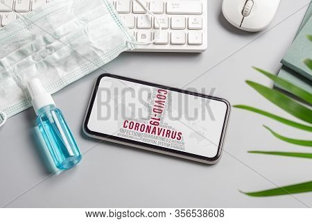 Coronavirus Or Covid-19 Outbreak Mockup Mobile Phone With Facial Masks And Alcohol Hand Gel On Offic