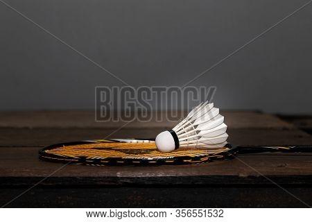 Closeup Shot Of White Badminton Shuttlecock And Racquet On Wooden Floor.