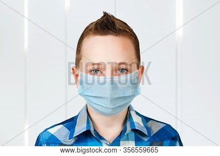 Unhappy, Sad Young Boy Wearing A Protective Face Mask Prevent Virus Infection Or Pollution
