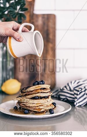 Lemon Poppy Seed Pancakes On Grey Plate. Fresh Blueberries On Top. Maple Syrup Drizzle. Stack Of War