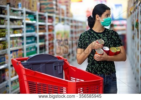 Alarmed Female Wears Medical Mask Against Coronavirus While Grocery Shopping In Supermarket Or Store