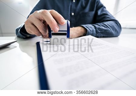 Close-up Of Person Hands Using Stamper On Document With The Text Approved