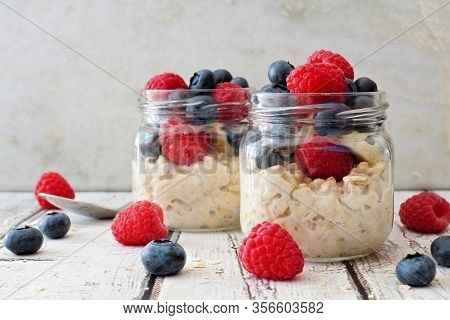 Overnight Oats With Fresh Blueberries And Raspberries In Jars On A Rustic White Wood Background