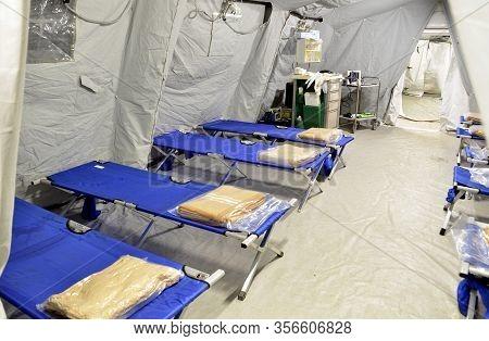 Empty Hospital Field Tent For The First Aid, A Mobile Medical Unit Of Red Cross For Patient With Cor