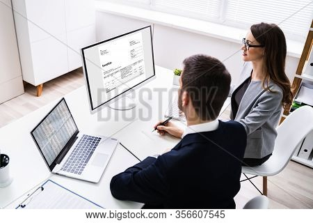 Close-up Of Two Businesspeople Analyzing Invoice On Computer