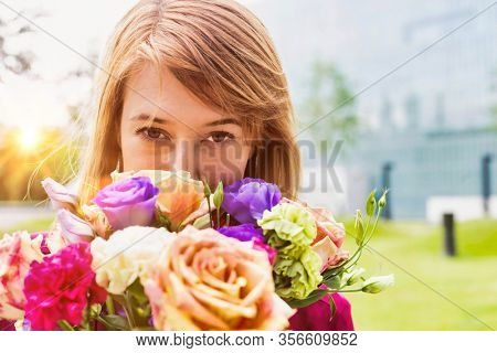 Portrait of young attractive woman holding and smelling boquet of flowers with yellow lens flare in background