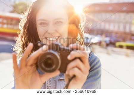 Young attractive woman holding camera and taking photo with lens flare in background