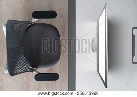 Modern comfortable workspace - computer desk with mockup white computer monitor and orthopaedic chair. Top view. Home working outside office concept.