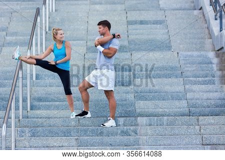 Young attractive couple stretching in stairs