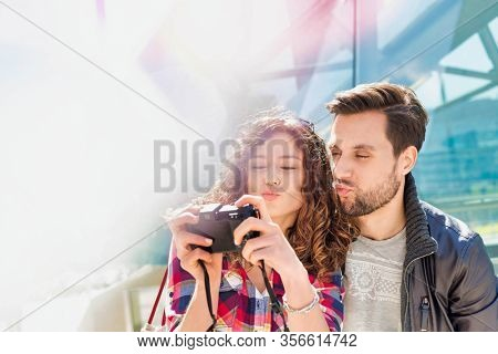 Portrait of young attractive woman taking selfie with her boyfriend in the middle of the city