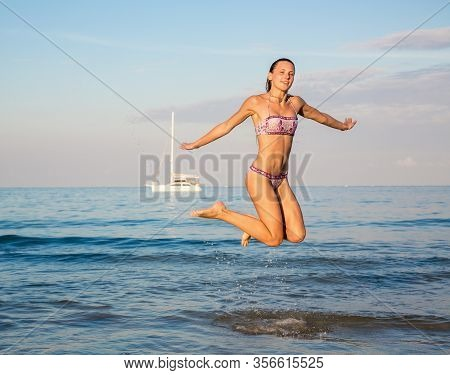Happy Young Woman In Jump On Beach