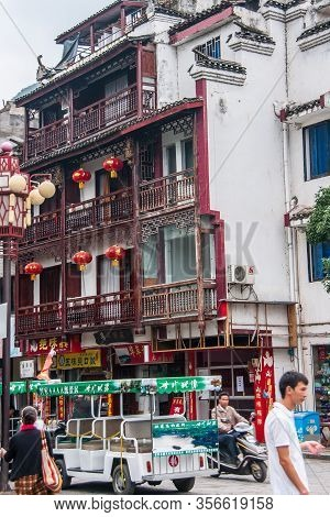 Guilin, China - May 10, 2010: Downtown. Traditional White Multistory House With Brown Wooden Balconi