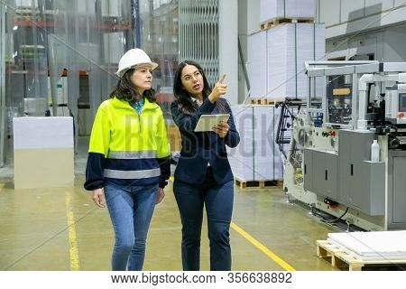 Female Technician And Manager Walking At Printing House. Concentrated Factory Workers Strolling At P