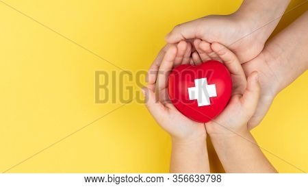 World Red Cross Day, Adult And Child Hands Holding Red Heart, Healthcare, Love And Family Insurance