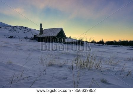 snow covered stone refuge of Galvarina Plateau in Etna Park at the sunset, Sicily