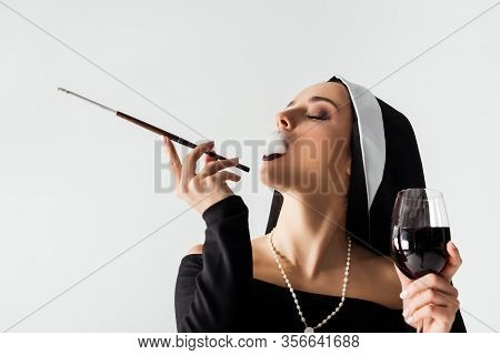 Attractive Sexy Nun With Glass Of Wine Smoking A Cigarette In Mouthpiece Isolated On Grey