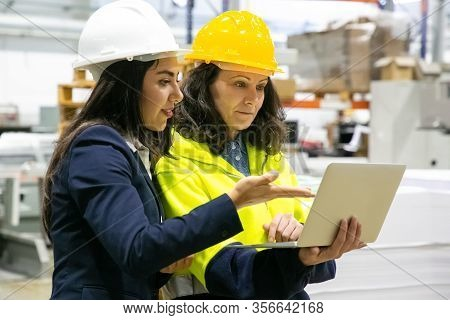 Confident Female Workers With Laptop At Manufacturing Plant. Two Female Employees Talking While Stan
