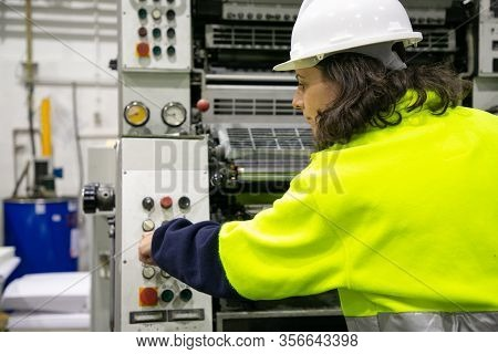 Professional Operator Working With Printing Machine. Confident Mature Woman Setting Printing Press.