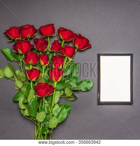 Bouquet Of Fresh Red Rose Flowers And Empty Photoframe On Black Background. Floral Composition, Mour