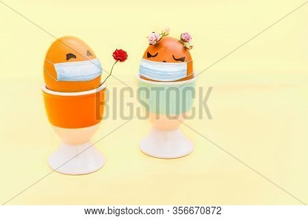 Happy Easter Eggs With Drawn Cartoon Faces And With Virus Mask On Light Yellow Background. Corona Vi