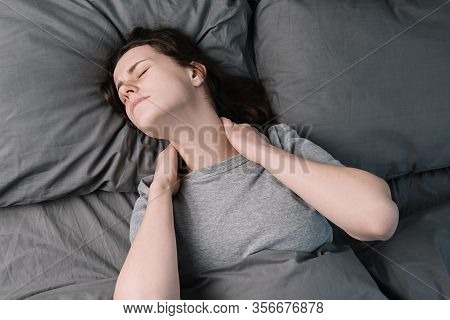 Tired Unhappy Young Woman Lying In Bed In Morning Feels Pain In Neck After Night Sleep, Massage Tens