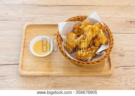 Padnoongo With White Sesame And Rice In A Container On A Wooden Tray And Condensed Milk On The Woode