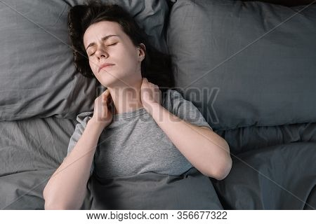 Top Close Up View Upset Young Woman Lying In Bed In Morning Feels Pain In Neck After Night Sleep, Aw