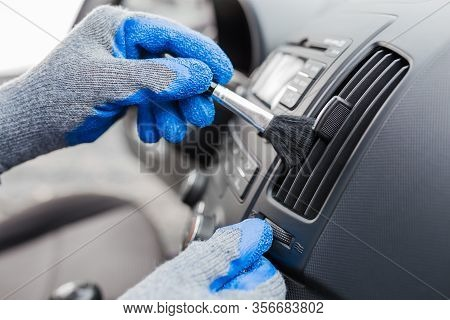 Man Hands Using Cleaning Brush And Removing Dust From Car Air Conditioning Vent Grille. Car Detailin