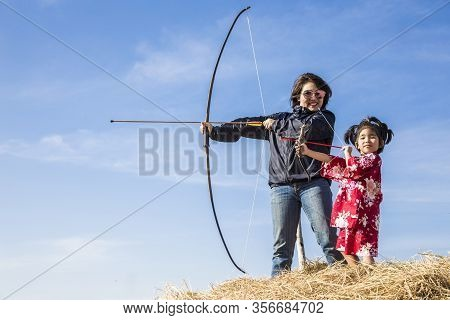 Asian Mother And Daugther Playing Arrow On Straw And Clear Sky