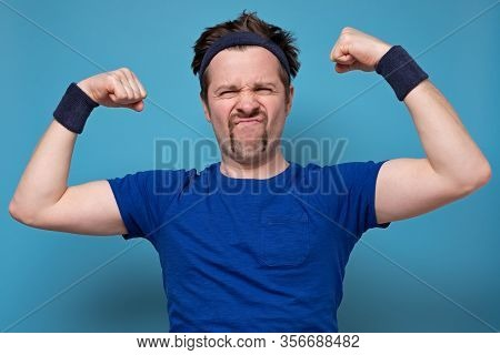 Young Handsome Funny Man Wearing Holding His Arm Up To Show How Strong He Is