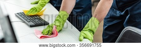 Partial View Of Cleaners In Rubber Gloves Cleaning Office Desk And Computer Keyboard