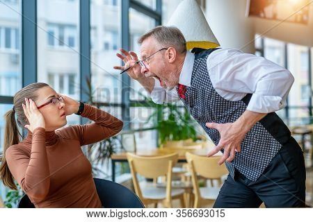 Enraged Businessman Expressing Dissatisfaction With Work On Frustrated Girl In Modern Office.
