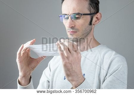 Adult Man Holding Hygienic Mask To Prevent Infection, Airborne Respiratory Illness Such As Flu, 2019