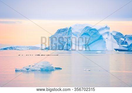 Blue Icebergs In Atlantic Ocean At Sunset In Saqqaq Village, Western Greenland. Flock Of Ducks Flowi