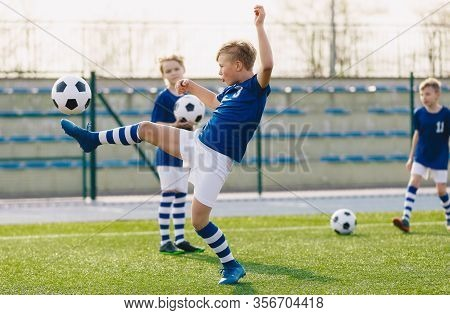 Young Boys In Sports Club On Soccer Football Training. Kids Enhance Soccer Skills On Natural Turf Gr