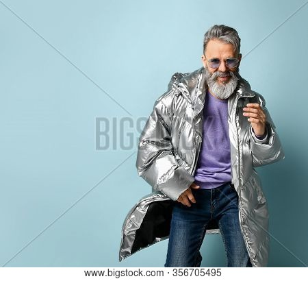 Rich Old Man In Purple Pullover And Sunglasses, Silver Colored Down Jacket, Jeans. He Is Running, Sh