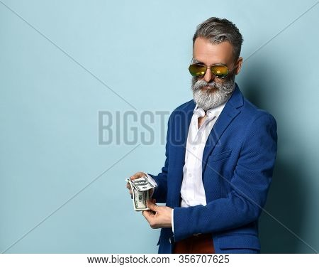 Savage Bearded Elderly Man In White Shirt, Jacket, Brown Pants And Sunglasses. He Is Showing A Fan O