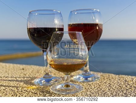 Sudak, Crimea - September 13, 2019: Three Glasses With Alcoholic Drinks On A Background Of The Sea.
