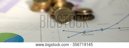 Close-up Of Valuable Metallic Currency Lying In Pile On Charts And Graphs Used To Analyze Successful