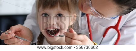 Portrait Of Cute Little Girl At Stomatologist Office. Doctor Examining Teeth Of Funny Kid. Doc In Me