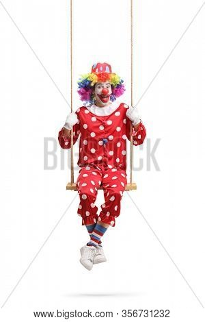 Cheeky clown swinging on a wooden swing isolated on white background