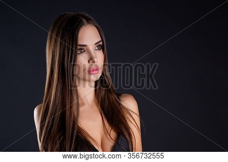 Portrait Of A Beautiful Woman In A Black Bra On A Black Background.