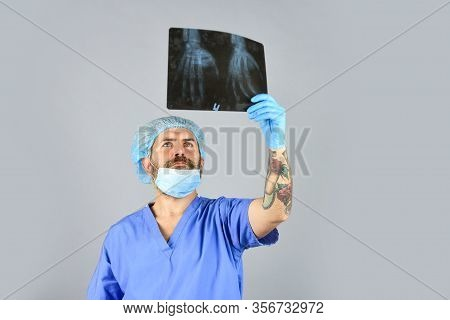 Surgery Operation And Medical Concept. Man Look At Roentgen. Radiologist Hold Xray. Doctor Examines