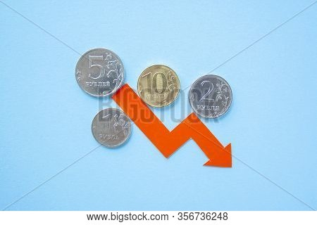 Many Rouble Coins On Blue Background With Red Arrow Down. Exchange Rate Chart. Ruble Depreciation. E