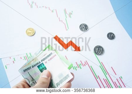 Male Hand Holding Rouble Bills On Exchange Rate Of Russian Ruble And Red Arrow. Ruble Depreciation.
