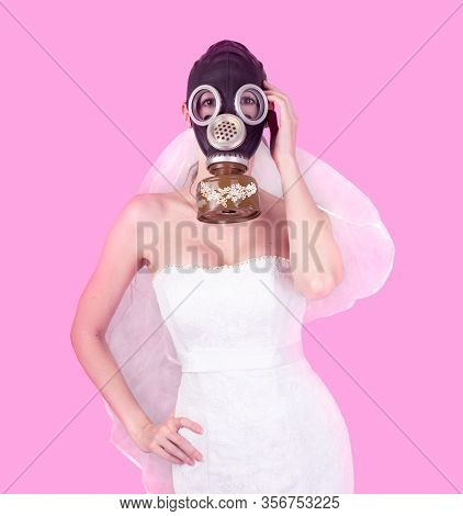 Bride In Veil Dress And Protective Mask In A Gas Mask Posing On A Delicate Background