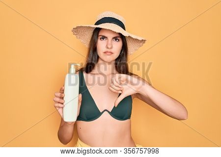 Young beautiful girl wearing swimwear bikini and summer hat holding sun protection cream with angry face, negative sign showing dislike with thumbs down, rejection concept